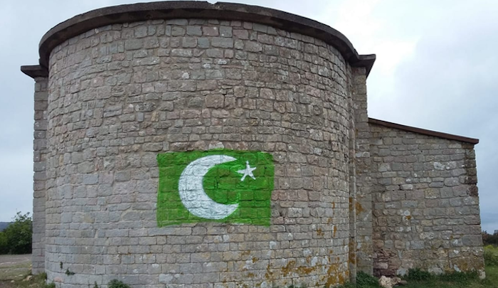 France: Pakistani flag painted on wall of 11th-century chapel